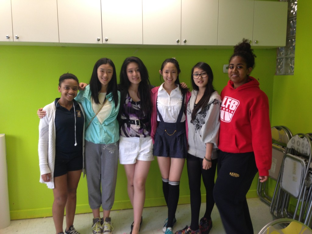 Six diverse teenage girls smile and pose with their arms around each other. The author, Jessie Guo, is second from left.