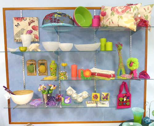 A selection of brightly-coloured goods for sale at the YWCA Toronto International Boutique, arranged on a shelf.