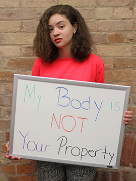 "Genevieve, author of the post, holds a sign that says ""My body is not your property"""